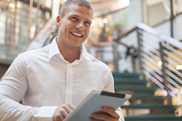 Smiling Man with tablet computer in modern business building