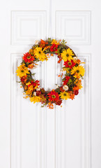 Colorful flower wreath hanging on white wood door
