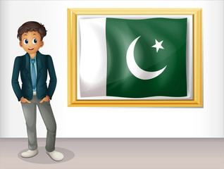 A man beside the framed flag of Pakistan