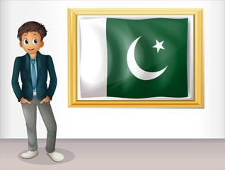 A man beside the framed flag of Pakistan
