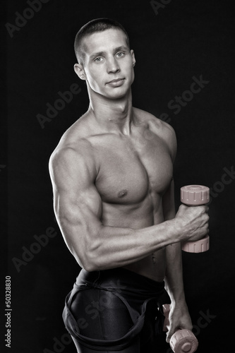 Black and white photo of sexy sportsman with dumbbells