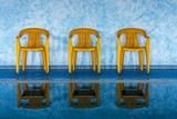 three yellow chairs at the swimming pool