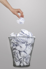 Woman hand throwing crumpled paper into a silver trash bin