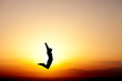 silhouette of teen jumping in sunset for fun