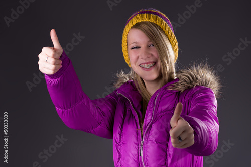 Teen in winterclothes thumbs up