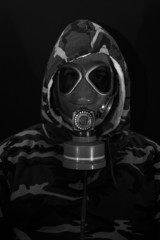Soldier in gas mask on black background