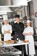 Team Of Confident Chefs In Industrial Kitchen