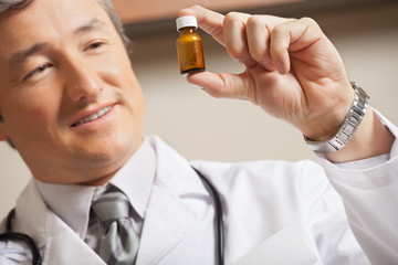 Doctor Looking At Medicine Bottle