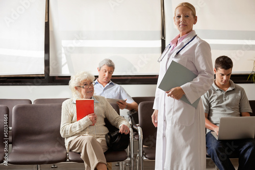Doctor With People In Hospital Lobby