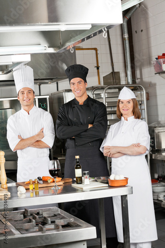 Team Of Confident Chefs In Industrial Kitchen