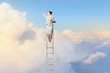 Businesswoman standing on ladder