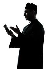man priest silhouette reading bible