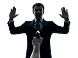 business man arms raised with gun pointing at him  silhouette