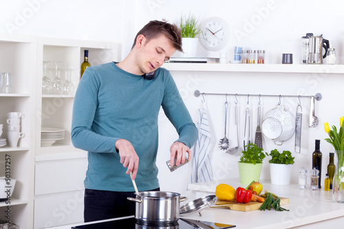 young man cooking a meal and talking on the phone in the kitchen