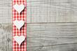 Drei weiße Herzen vor Holzhintergrund