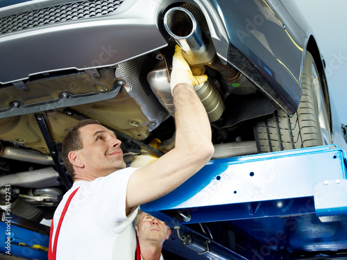 Two car mechanics fixing the exhaust system of a car