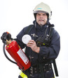 firefighter is showing a smoke detector and extinguisher
