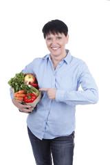 Ältere Frau zeigt auf Tüte mit Salat und Gemüse