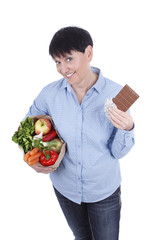 Ältere Frau überlegt zwischen Schokolade und Gemüse