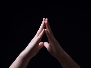 Hands together on a black background
