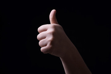 Thumb up on black background