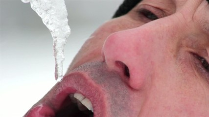 man drinks water from melted icicles