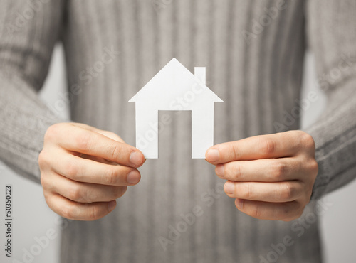man holding paper house