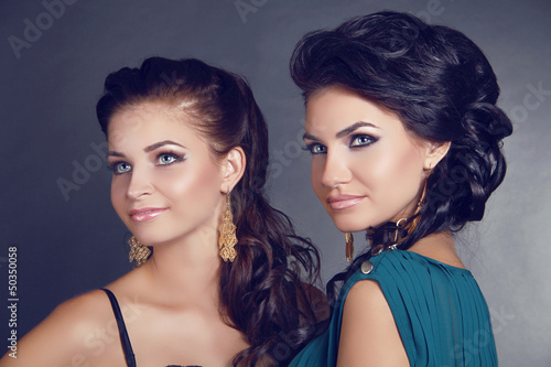 Attractive beautiful two women portrait looking away on gray bac