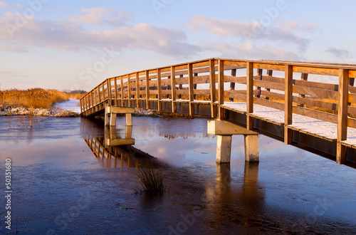 wooden bridge through frozen river