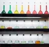 Colorful liquid in flasks laying on shelf