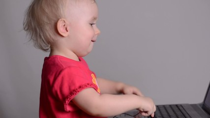 Cute baby girl using a laptop computer