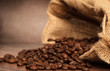 Coffee beans in coffee bag made from burlap on wooden surface