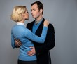 Man in jacket embracing woman in blue cardigan isolated on grey