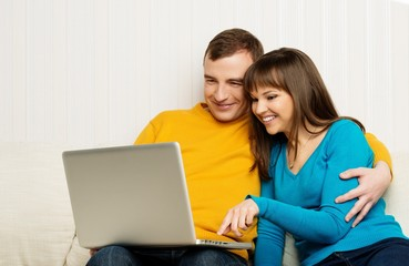 Smiling man and woman with laptop