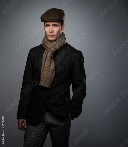 Young man in brown jacket wearing cap and scarf isolated on grey