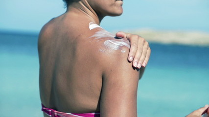 Woman applying sun lotion on her shoulders, slow motion shot at