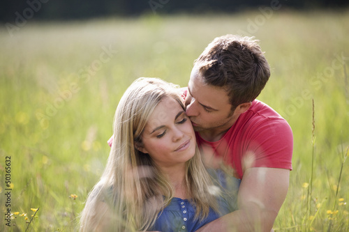 A young couple sitting in long grass embracing
