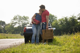 A couple standing in front of a sports car with a picnic basket