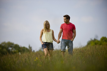 A young couple walking hand in hand through a field