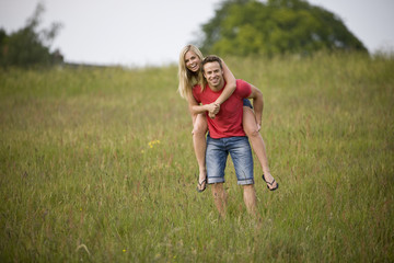 A young man giving his girlfriend a piggyback through a field