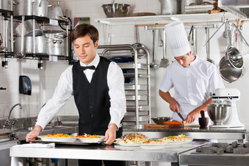 Waiter And Chef Working In Kitchen