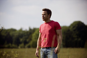 A young man standing in a field in summertime