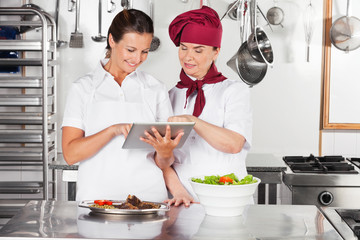 Happy Female Chefs Using Digital Tablet