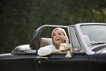 A young woman in a sports car speaking on a mobile phone