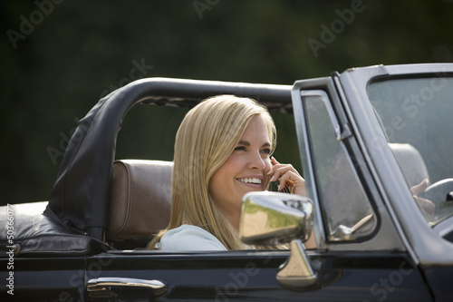 A young woman in a black sports car using a mobile phone