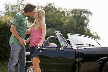 A young couple standing in front of a black sports car kissing