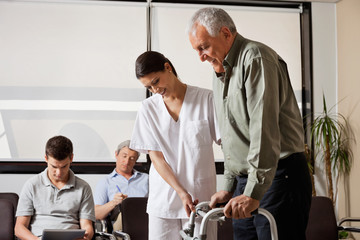 Man Being Assisted By Nurse To Walk Zimmer Frame