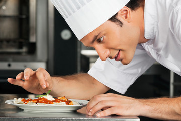 Male Chef Garnishing Dish