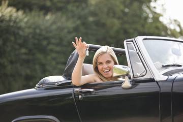 A young woman sitting in a black sports car holding the keys