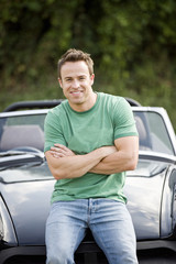 A young man sitting on the bonnet of his black sports car